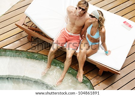Over head view of an attractive couple sunbathing and wearing sunglasses while sharing a sun bed by a swimming pool. - stock photo