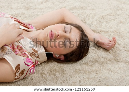 Over head view of an attractive young woman laying down on a furry carpet at home, listening to music with her earphones, relaxing with her eyes closed. - stock photo