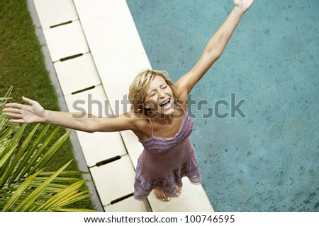 Over head view of an attractive young woman smiling under the rain with arms outstretched, looking up by a swimming pool. - stock photo