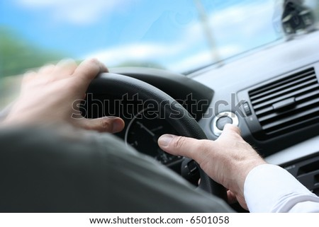 Over shoulder view of a man driving a car with his hands on the steering wheel, turning quick. (sunny weather) - stock photo