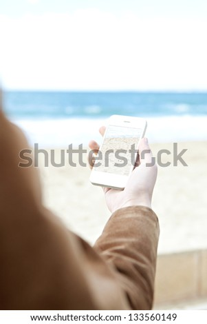 "Over shoulder view of a woman's arm and hand holding a modern ""smart phone"" while taking pictures of the sea on a golden beach."