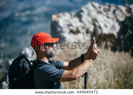 Over shoulder view of backpacker taking shot on cell of his dog on rocks