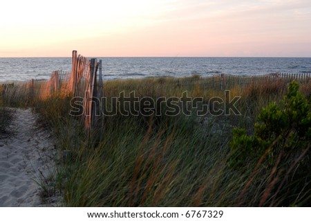 Over the sand dune and to the beach. - stock photo