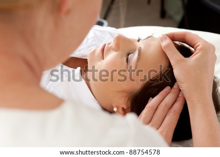 Over the shoulder shot of professional acupuncturist placing needle in face of patient - stock photo