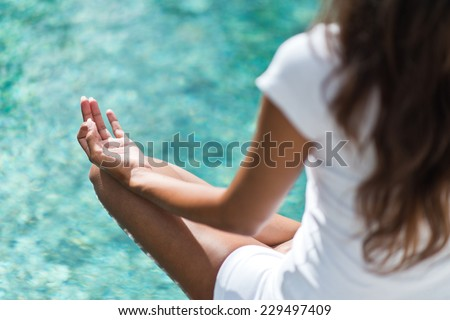 Over the shoulder view from behind of a long haired young woman meditating above a calm sea with focus to her hand resting on her knee in the lotus position - stock photo