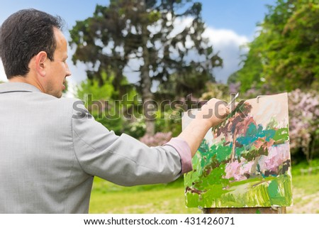 Over the shoulder view from behind of a male painter working on a sketchbook painting a garden scene with flowers outdoors - stock photo
