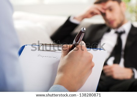 Over the shoulder view, of a business man sit on a couch talking to his psychiatrist - stock photo