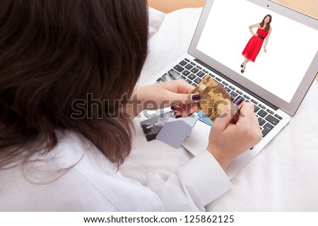 Over the shoulder view of a woman purchasing a dress online with her credit cards - stock photo