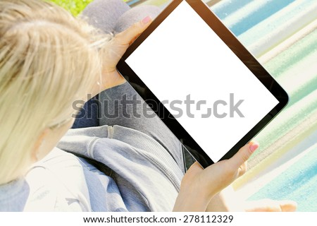 over the shoulder view of a woman relaxing in a hammock using a digital tablet