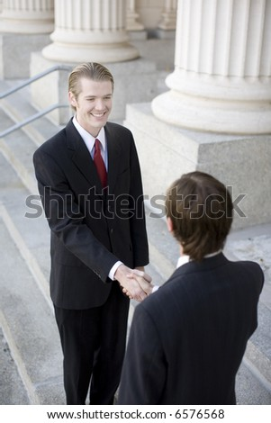 over the shoulder view of two businessmen on the steps of courthouse shaking hands - stock photo