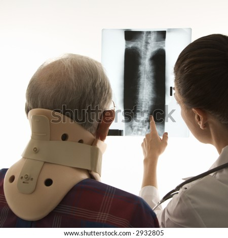 Over the shoulders view of mid-adult Caucasian female pointing at an x-ray as elderly Caucasian male in neck brace looks on. - stock photo