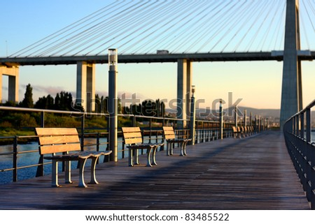 Over-water boardwalk near Vasco da Gama bridge, at Park of Nations, in Lisbon, Portugal. Photo taken right after the sunrise. Shallow depth-of-field, focus on foreground. Image unsharpened. - stock photo