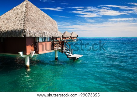 Over water bungalow with steps into green clear ocean - stock photo