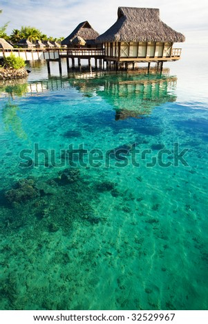 Over water bungalows over amazing lagoon with coral - stock photo