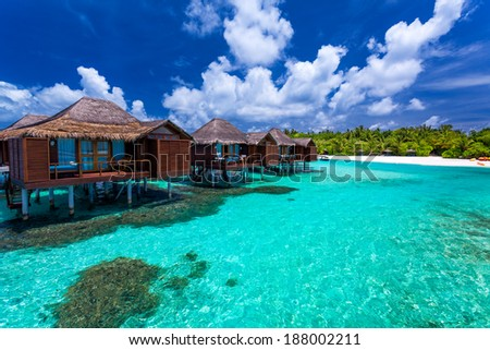 Over water bungalows with steps into amazing green lagoon with coral - stock photo