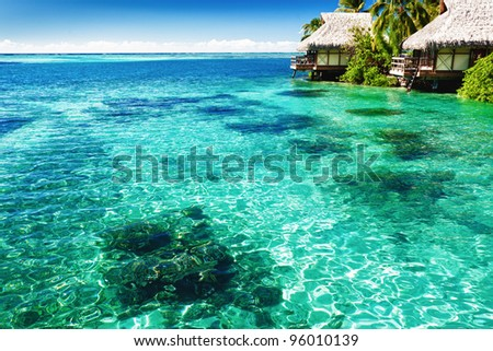 Over water bungalows with steps into green tropical lagoon - stock photo