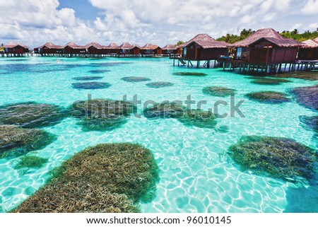 Over water bungalows with steps into lagoon with coral - stock photo