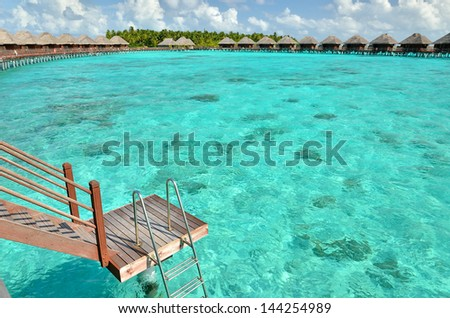 Over water villas with steps into the green lagoon -- maldives tropical island resort  - stock photo