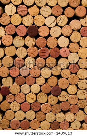 Over 100 wine corks stacked up showing the bottoms and tops. Some stained red from the wine. - stock photo