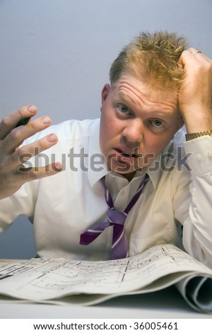 Over worked man looking at house plans