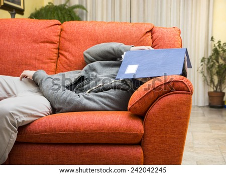 Over-worked, tired young man at home sleeping instead of working or studying, resting with head covered by book - stock photo