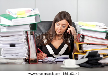 over-worked woman in office - stock photo