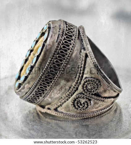 over 100 years old antique Turkish tribal ring with grunge pattern and blue stones on textured background - stock photo