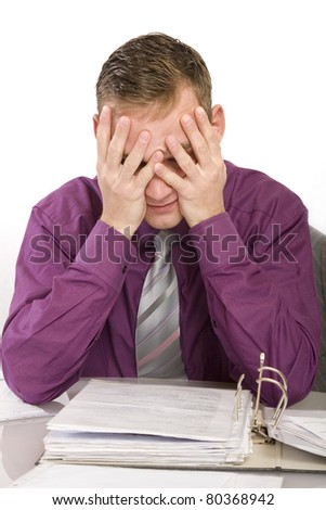 overburdened and desperate businessman in the office. He holds her hands over her face. - stock photo