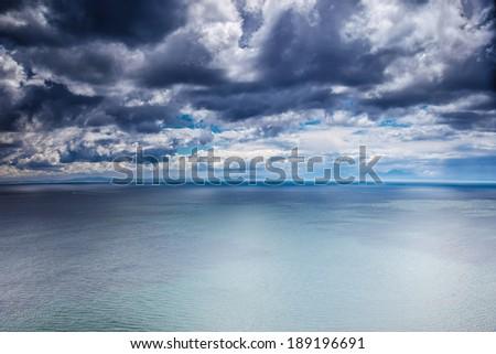 Overcast weather over sea, dark dramatic cloudy sky, dangerous seascape, panoramic landscape - stock photo
