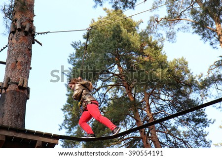 Overcoming obstacles. Little girl climbing on a rope.