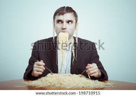 Overeating and consumerism concept. Silly nasty businessman eating pasta. - stock photo