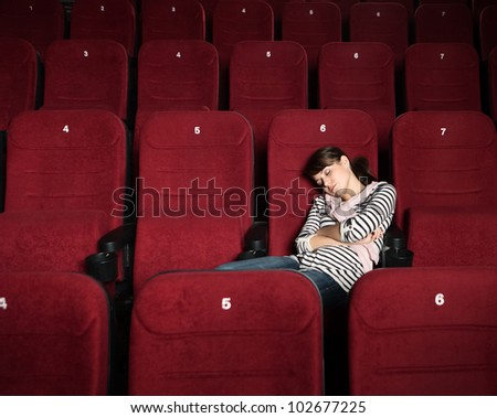 Overexhausted woman in the movie theater - stock photo