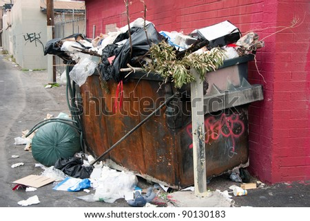 overfilled trash dumpster in ghetto neigborhood - stock photo