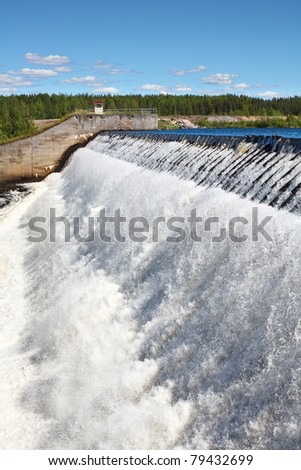 Overflow of water on the man-made storage pond - stock photo