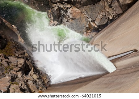 Overflow water gushing out of the Hetch Hetchy dam in Yosemite, California. - stock photo
