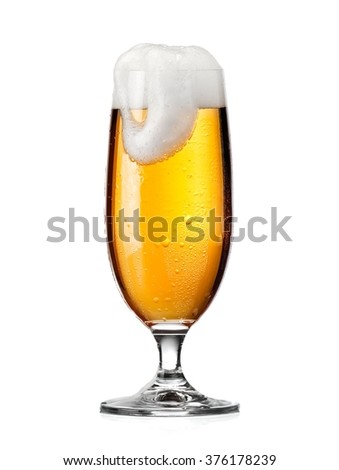 Overflowed glass of beer - stock photo