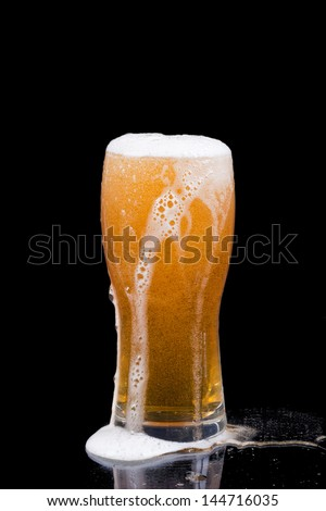 Overflowing beer glass - stock photo