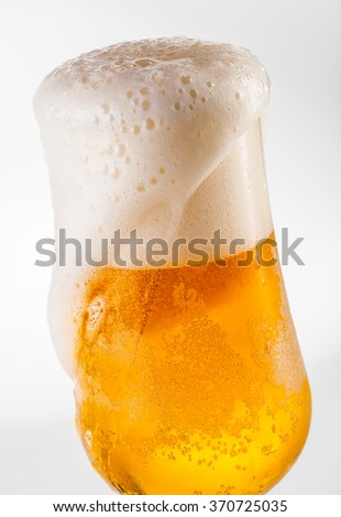 Overflowing beer in a tulip glass - stock photo