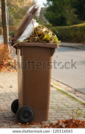 Overflowing brown garbage bin or can full with dead autumn leaves and plants - stock photo