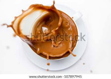 Overflowing cup of white coffee against white background - stock photo
