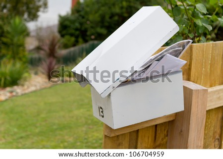 Overflowing full white metal letterbox on fence post - stock photo