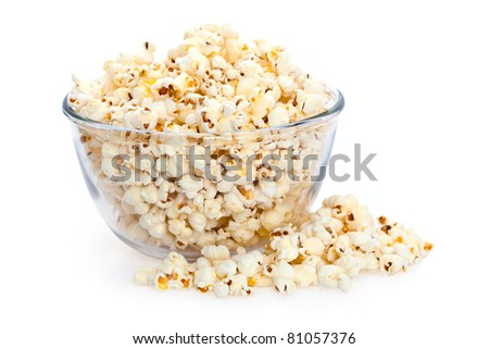 Overflowing glass bowl of freshly popped popcorn isolated on white background