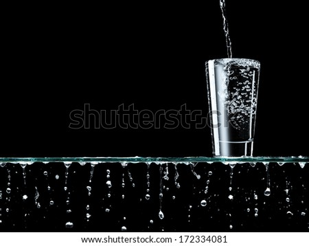 Overflowing glass of water  - stock photo