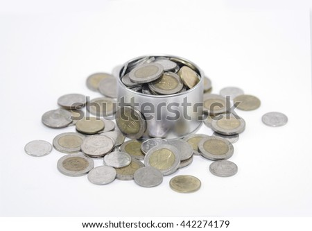 Overflowing jar of Thai coins, isolated on white background.