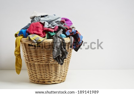 Overflowing laundry basket. Household chore concept on white background - stock photo