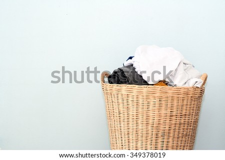 Overflowing laundry wicker basket. Household chore concept on gray background - stock photo