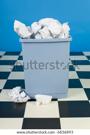Overflowing trashcan with crumpled paper. Front view - stock photo