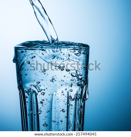 overflowing water in a glass - stock photo