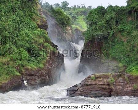 overgrown rock formation at the Murchison Falls in Uganda (Africa) - stock photo