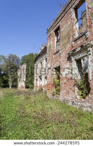 Overgrown ruins of an old manor house - stock photo